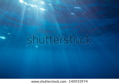 Underwater shot with sunrays in deep tropical sea - stock photo