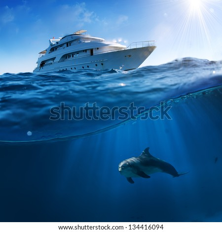 Underwater splitted by waterline postcard template. Bottlenose dolphin swimming under boat - stock photo