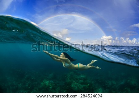 Underwater Sport Postcard. A freediver floating under water surface in ocean. A rainbow appear on cloudy sky over beautiful seascape - stock photo