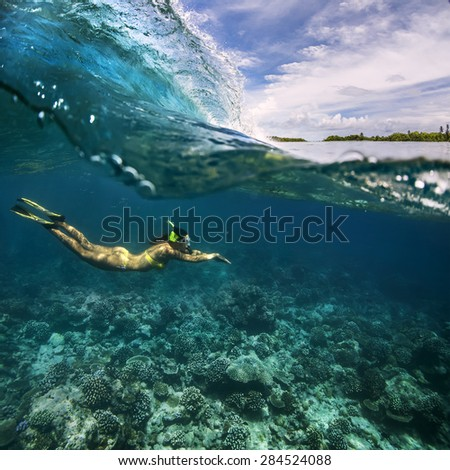 Underwater Sport Postcard. A freediver floating under water surface in ocean. Female model using fins and snork diving with surfing wave. - stock photo