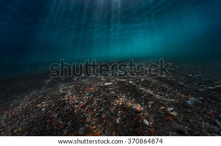 Underwater view of the sea surface with sunbeams and bottom with gravel - stock photo