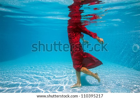 Underwater woman fashion portrait with red dress in swimming pool.