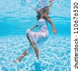 Underwater woman fashion portrait with white dress in swimming pool. - stock photo