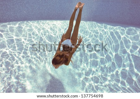 Underwater woman portrait with white bikini in swimming pool. - stock photo