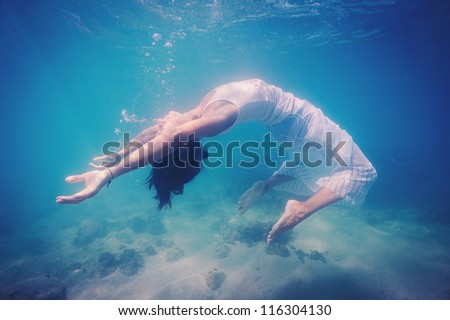 Underwater woman portrait with white dress into the sea. - stock photo