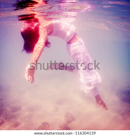 Underwater woman portrait with white dress into the sea.