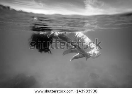 Underwater woman portrait with white dress into the sea. Black and white image. - stock photo