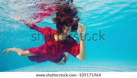Underwater woman with red dress in swimming pool. - stock photo