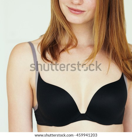Underwear concept. Smiling young sexy woman with red hair in lingerie posing on white background. Natural beauty. Close up