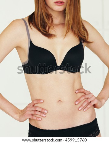 Underwear concept. Young sexy woman with red hair in lingerie posing on white background. Close up