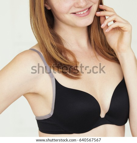 Underwear concept. Young smiling sexy woman with red hair in lingerie posing on white background. Hand near face. White teeth. Natural style. Close up