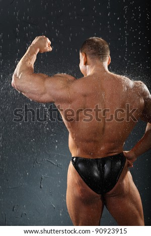 Undressed bodybuilder stands in rain back to camera and shows muscles of hand - stock photo