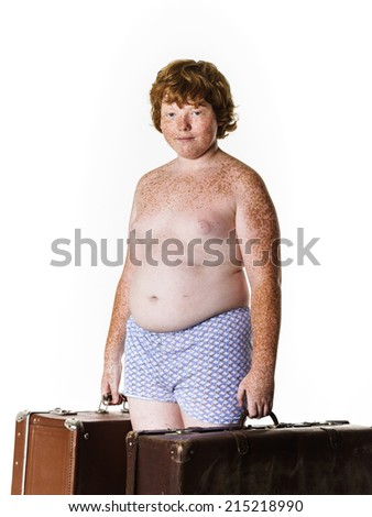 Undressed poor red-haired boy with old suitcases isolated on white