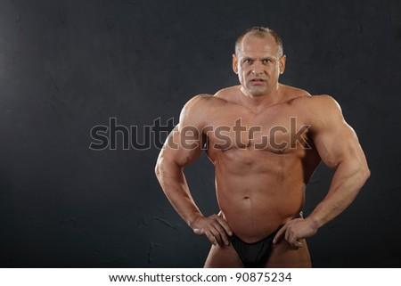 Undressed tanned wet bodybuilder. - stock photo