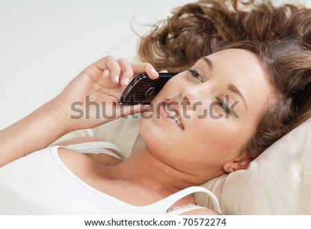 Undressed young woman lying in bed and talking on cellphone