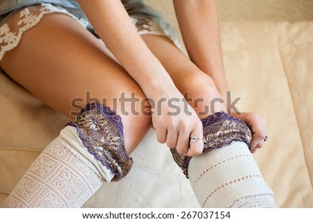 Undressing girl. Sensual women get her hose down - stock photo