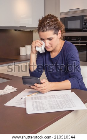 Unemployed and divorced woman with many debts reviewing her monthly bills