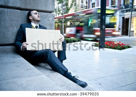 Unemployed businessman holding a blank cardboard sign with blurred background