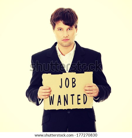 Unemployed businessman with cardboard sign - stock photo