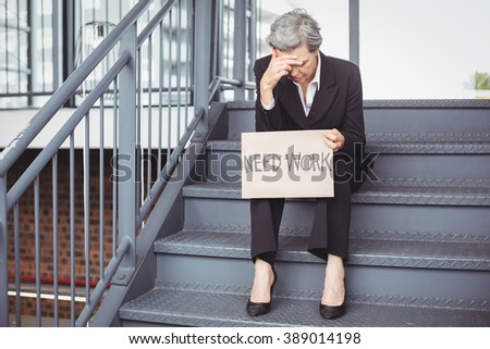 Unemployed businesswoman holding need work placard while sitting on steps - stock photo