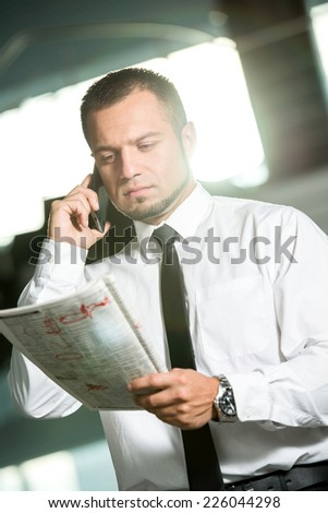 Unemployed man is looking for a job in the newspaper and calling. - stock photo