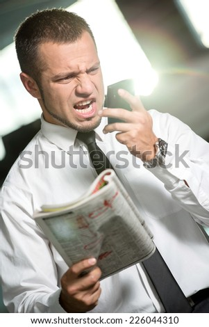 Unemployed man is looking for a job with newspaper and screaming into the phone. - stock photo