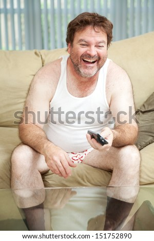 Unemployed man laughing and watching a funny show on television.   - stock photo