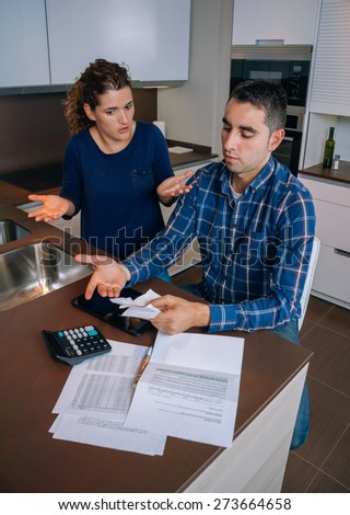 Unemployed young couple with many debts reviewing their bills. Financial family problems concept. - stock photo