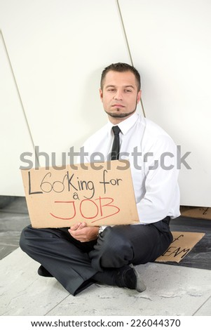 Unemployment. Young businessman is squatting with sign Looking for a job, outdoors. - stock photo