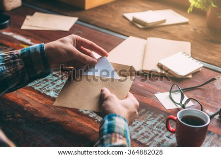 Unexpected letter. Close-up image of man opening an envelope while sitting at the rustic wooden table  - stock photo