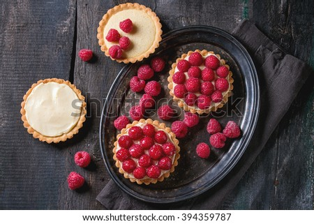 Unfinished and ready to eat tartlets with custard and fresh ripe raspberries, served on vintage metal tray with baking forms and textile napkin over old wooden table. Dark rustic style. Flat lay