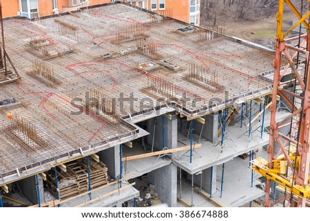 Unfinished apartment floor with steel rods and concrete under construction with wood high up in the air - stock photo