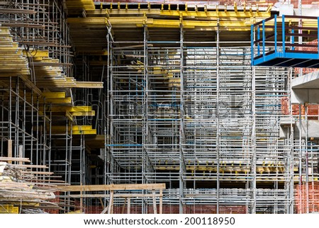 Unfinished concrete building under construction with scaffolding - stock photo
