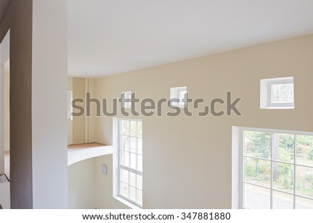 Unfinished construction interior of living room with big and small windows and balcony.  - stock photo
