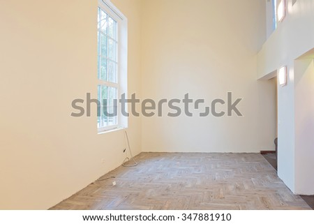 Unfinished construction interior of living room with tile wooden floors, big window and balcony.  - stock photo