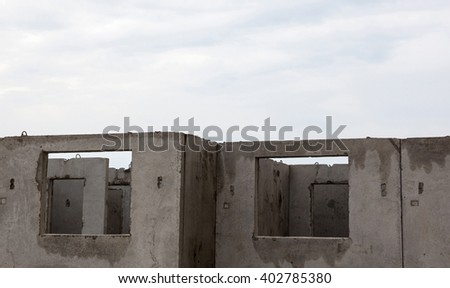 Unfinished grey concrete building in the construction site. - stock photo