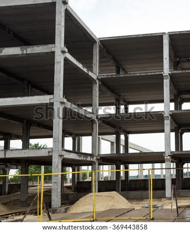 Unfinished grey concrete framework of the future building in the construction site - stock photo