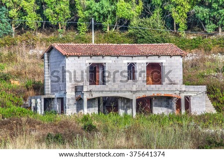unfinished house in the countryside on a clear day - stock photo