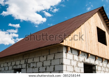 Unfinished house of the blocks with roof of tiles and wooden loft under a blue sky - stock photo