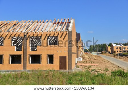 Unfinished houses of brick under construction site with wooden roof stone and concrete - stock photo