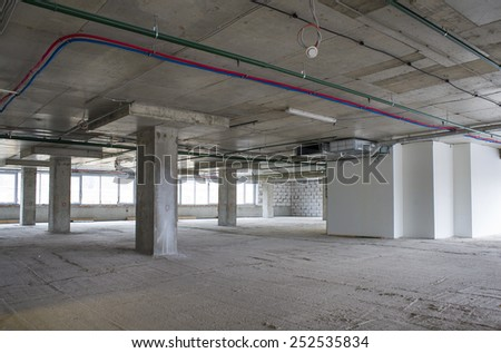 Unfinished interior of business center under construction in grey colours - stock photo