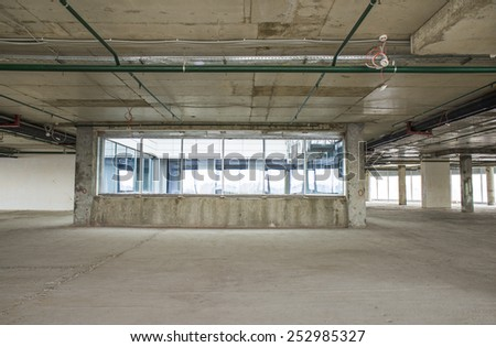 Unfinished interior of business center under construction in grey colours. Lift shaft