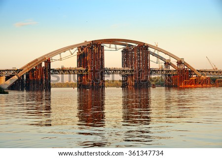 Unfinished iron bridge over the river - stock photo
