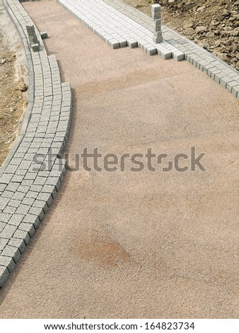 Unfinished pavement path being laid from concrete pavement blocks with mineral topping