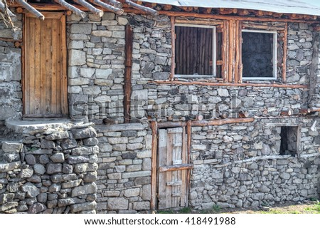 Unfinished stone house with wooden door and windows closeup - stock photo
