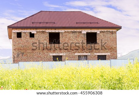 unfinished two-storey brick house in the nature - stock photo