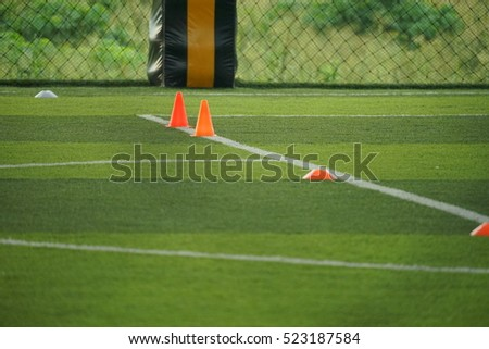 Unfocused football field background with orange cone and green grass at day time.