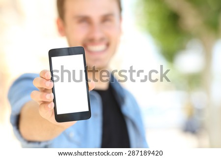 Unfocused man hand showing to you a blank phone screen in the street - stock photo