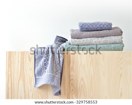Unfolded and folded grey towels on cupboard.