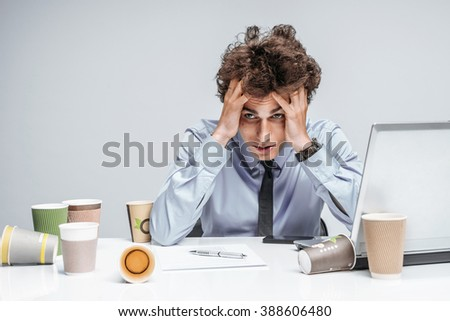 Unfortunate manager dissatisfied with his work. Modern businessman at the workplace working with computer, depression and crisis concept - stock photo